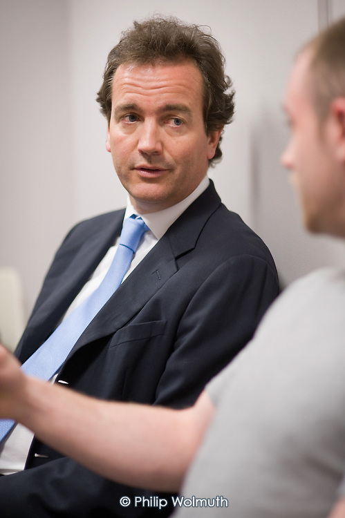 Conservative MP Nick Hurd, newly appointed Minister for Civil Society, speaks to young men being helped back into employemnt during a visit to projects in Church Street, London,  supported by the Paddington Development Trust.