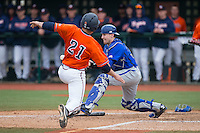 Tyler Boyd (30) of the Seton Hall Pirates fields a throw as Matt Thaiss (21) of the Virginia Cavaliers slides into home plate at The Ripken Experience on February 28, 2015 in Myrtle Beach, South Carolina.  The Cavaliers defeated the Pirates 4-1.  (Brian Westerholt/Four Seam Images)