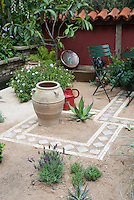 Creating an outdoor patio with sand and tiles, using water-wise succulent plants and drought tolerant herbs such as lavender Lavandula, with raised beds of perennial flowers, Laburnum tree in bloom, low wall, patio furniture, ornamental urn, for xeriscaping landscaping
