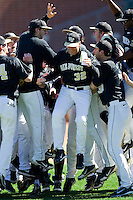 Wake Forest Demon Deacons head coach Tom Walter (32) leaps into a huddle of his players prior the the start of their game against the Youngstown State Penguins at Wake Forest Baseball Park on February 24, 2013 in Winston-Salem, North Carolina.  (Brian Westerholt/Four Seam Images)