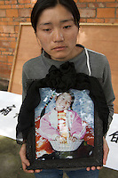Desperate mother He Xiaofang, 30, poses for pictures with photos of her died single child Xu Ziling, 10. Parents of the children victims prepare a petition banner accusing the poor quality of the school building which collapsed during the earthquake causing about 200 out of 309 children die in Fuxin town, Mianzhu city. 18 May, 2008, the sixth day after the 7.8 magnitude earthquake in Mianzhu, Sichuan, China. The earthquake happened at 14:28pm on 12 May 2008, with the epicenter in Wenchuan County, about 159km NW of Chengdu, Sichuan, China..18 May 2008