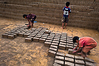 Peruvian children collect raw bricks for burning at a brick factory in Huachipa, a suburb in the outskirts of Lima, Peru, 10 August 2012. Child labour is a common practice at the artisanal brick factories, found predominantly in socially deprived areas of the urban zones. Poverty and lack of employment force parents, mainly season workers coming from rural areas of the country, to employ their own children, in an effort to ensure the livelihood for the whole family. Children aged 4-7 take part in simple jobs while children aged 8 and up tend to work regularly, same as adults. A family group, consisting of 2 adults and 2-3 children, may earn 20-25 USD per day, working almost the whole day, often in harsh climatic conditions.
