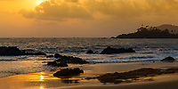 Colorful sunset on Patnem and Palolem beaches, with rock and palm tree silhouettes and the sun reflecting on the golden sand, in Goa India