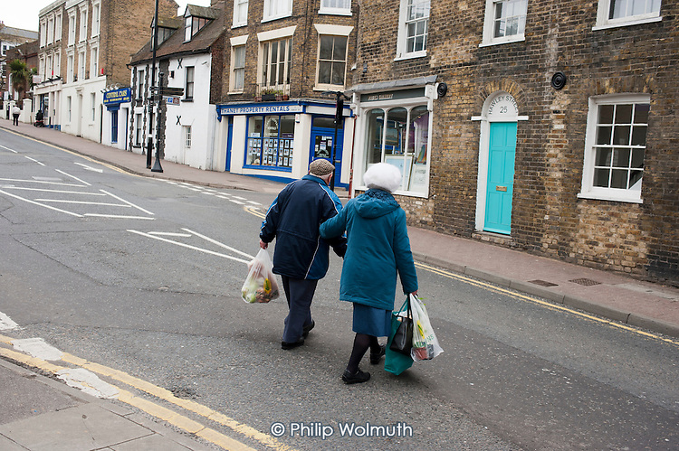 An elderly couple carrying shopping cross a road in Margate, Kent.