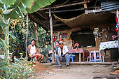 Osa Peninsula, Costa Rica. Family sitting outside their rainforest home.