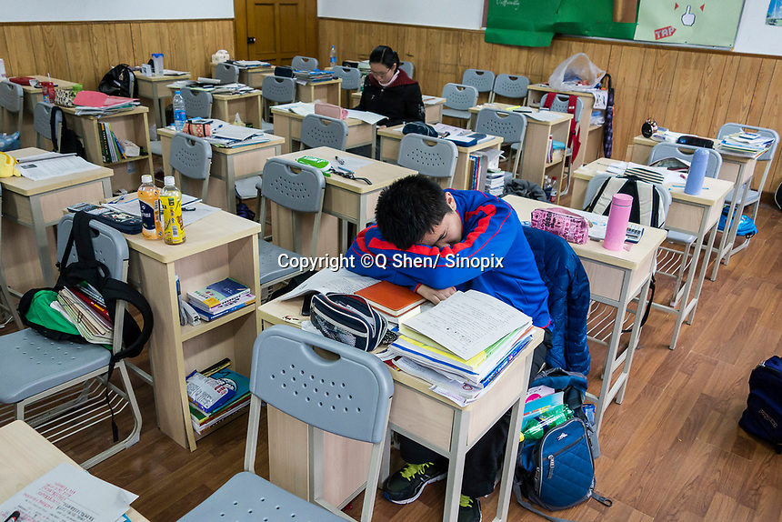 A student catches a quick nap during a meal break at the prestigious Shanghai High School in Shanghai, China on 27 February, 2014.  As one of the most demanding and exclusive high school in the country, Shanghai High School puts grueling study hours on its students, academic studies often last from 6:45 Am to as late as 9 PM.