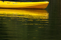 A bright yellow boat and its reflection float in Lake Chabot Regional Park on a warm summer afternoon.