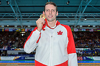 Ryan Cochrane of CAN pose with 1500 meter freestyle gold medal, Tuesday, July 29, 2014 in Glasgow, United Kingdom. (Mo Khursheed/TFV Media via AP Images)