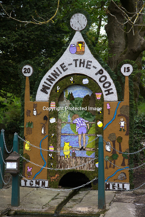 14/05/15<br /> <br /> Winnie the Pooh's 100th anniversary was the inspiration behind this year's Town Well.<br /> <br /> To mark ascension day this year's well dressings are unveiled and blessed by the local clergy in the Derbyshire village of Tissington in the Peak District National Park.<br /> <br /> Before today's blessings, wooden boards coated in clay are decorated with tens of thousands of petals, leaves and pieces of foliage to create the giant intricate mosaics. The boards,  take teams of many villagers three days to make. <br /> <br /> The village has been decorating its six wells every year for more than six hundred years. The tradition is believed to be a celebration of the wells never running dry, giving life and  sustaining the village during times of plague. After a church service today (Thursday)  clergy from six parish will bless each of the well.  <br /> <br /> Following in Tissington's footsteps many other villages in the Derbyshire area also have their own well dressing traditions.<br /> <br /> <br /> All Rights Reserved: F Stop Press Ltd. +44(0)1335 418629   www.fstoppress.com.