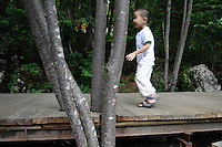 A young boy walk across a boardwalk in the Jiuzhaigou National Park. Sichuan Province. China.