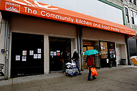 NEW YORK - NEW YORK - APRIL 12: People walk next to Food Bank for NYC, Community Kitchen an Food Pantry branch on April 12, 2021 in New York. According to the Food Bank for New York City during the pandemic, about 40 percent of the city's soup kitchens and pantries have been forced to close permanently. (Photo by John Smith/VIEWpress)