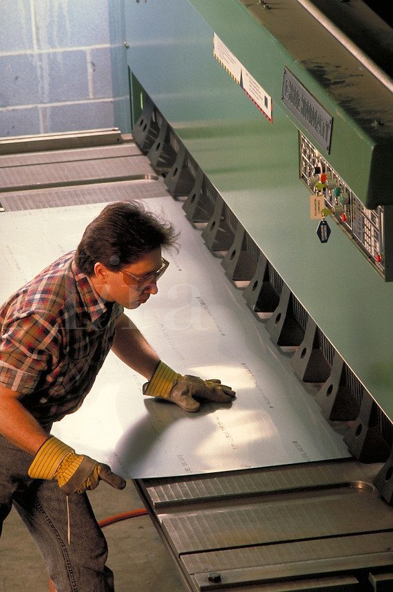 Sheet Metal Manufacturing. man pulling pushing a sheet into out of machinery. occupations, construction materials, fabrication,.