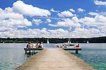 Germany, Bavaria, Upper Bavaria, Lake Starnberg: young people sitting on landing stage