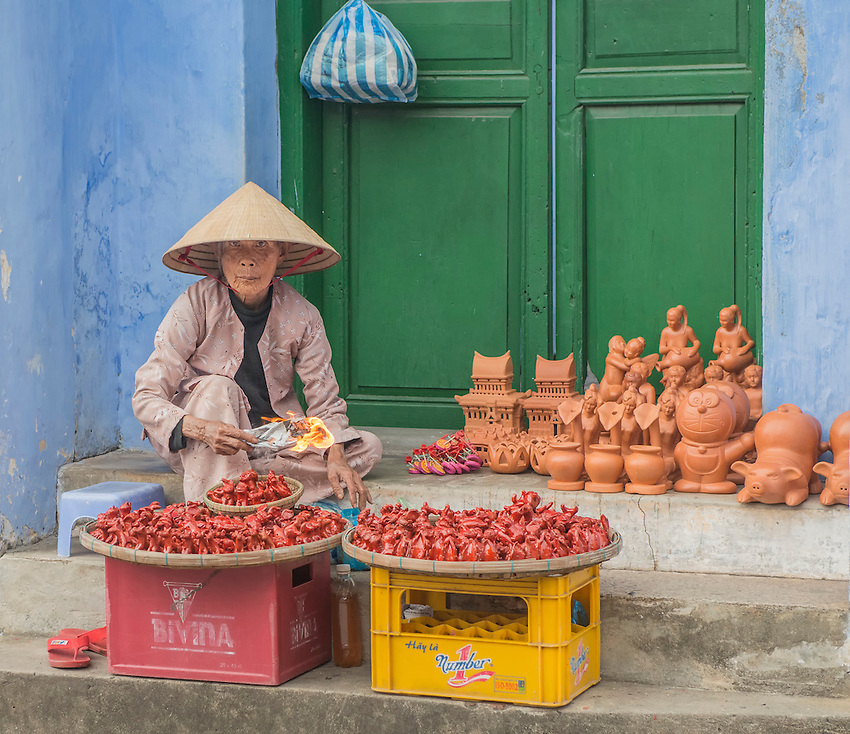 A woman sells her wares on the side of a street in Hoi An, Vietnam