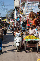 India, Dehradun.  Woman on Motorbike Buying Fruit from a Street Vendor.