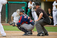Humberto Quintero (35) of the Tacoma Rainiers behind the plate with home plate umpire Nick Bailey as the Tacoma Rainiers faced the Salt Lake Bees at Smith's Ballpark on July 9, 2014 in Salt Lake City, Utah.  (Stephen Smith/Four Seam Images)