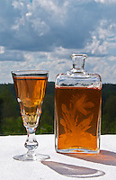 Swedish traditional aquavit schnapps glass in pointed form filled to the brim with spiced vodka, brannvin. A blue and cloudy summer sky in the background. A glass flask plunta with decorative engravings. Sweden, Europe.