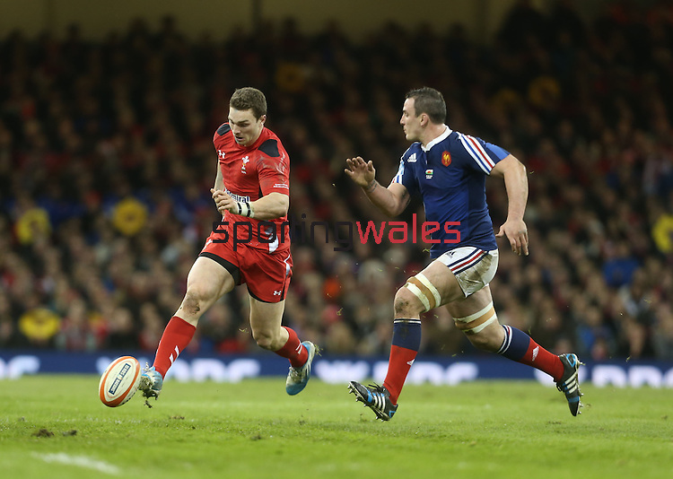 Wales center George North kicks the ball past French number 8 Louis Picamoles.<br /> RBS 6 Nations 2014<br /> Wales v France<br /> Millennium Stadium<br /> 21.02.14<br /> <br /> ©Steve Pope-SPORTINGWALES