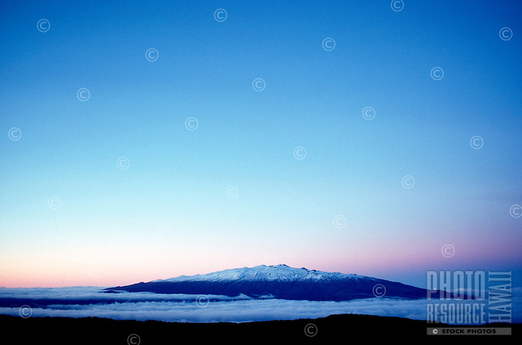 Summit of Mauna Kea seen from the lava fields of Mauna Loa at dusk, with clouds gathering in the saddle between the two volcanoes