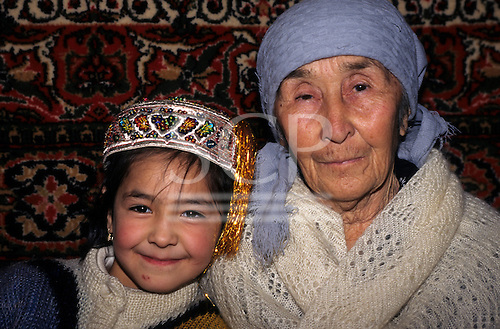 Uzbekistan. Old woman and little girl with carpet wall hanging behind.