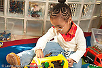 Education preschool 3-4 year olds girl sitting and playing by herself with toy plastic bus and human figures horizontal