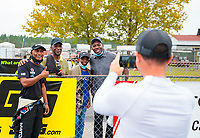 Sep 27, 2020; Gainesville, Florida, USA; NHRA top fuel driver Antron Brown (left) poses for a photo with fans during the Gatornationals at Gainesville Raceway. Mandatory Credit: Mark J. Rebilas-USA TODAY Sports