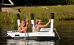 COLEBROOK, CT--- -090515JS11- Sophia D'Urson, 12, left, and Ellie Oakes-Rogers, 13, paddle the Titanic themed boat from the Colebrook Congregational Church through the course during the annual Colebrook Fair's cardboard boat regatta Saturday at the Colebrook Town Pond. <br />  Jim Shannon Republican-American