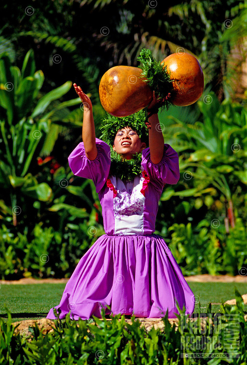A beautiful hula dancer wearing a traditional dress chants with her ipu heke (gourd instrument) outdoors at Lanikuhonua on Oahu's leeward side.