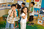 Preschool 4-5 year olds  music activity group doing hand gestures to song