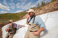 150620-JRE-7981E-0449 Cal Trout, right, and Joshua Quong, left, both teachers and quail hunting guides from Mississippi, stop to eat late-June snow while hiking into a remote interior Alaska stream to fly fish for Arctic Grayling.