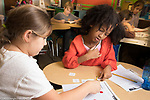 Public elementary school for gifted children classroom scenes two girls working together on hands on math activity, using round plastic counters as placeholders