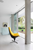 A spacious living room with full height glass sliding doors allowing access to the garden. A vibrant yellow retro chair provides an accent of colour against the otherwise white room.