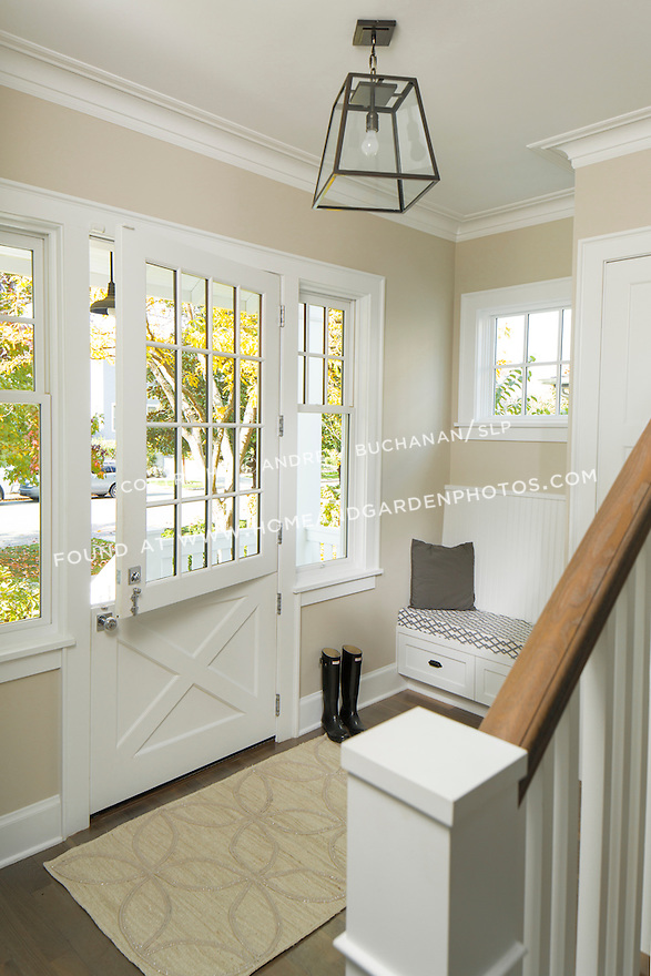 A beautiful dutch door adds an old-fashioned element to the entry of this traditional home.