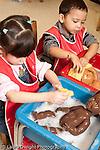 Education preschool 3-4 year olds boy and girl side by side washing dolls
