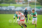 Adam Mac Amhlaoibh of An Ghaeltacht clearing his defence as Na Gaeil's Dan Goggin and Tomás OhAinféin gives chase in the Intermediate Club Football Championship