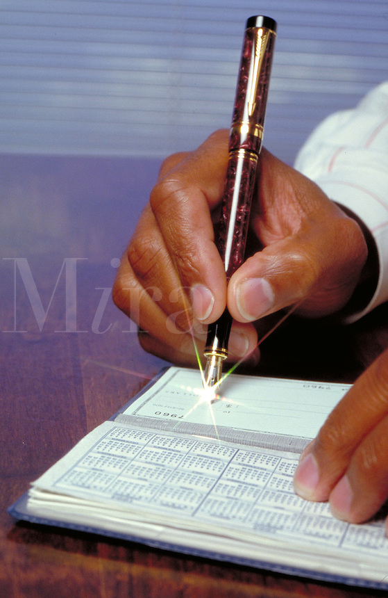 Close up of a Black man's hand signing a check with a starburst at the tip of the pen, finance, banking, African American. R. Williams M.R. #R-8.