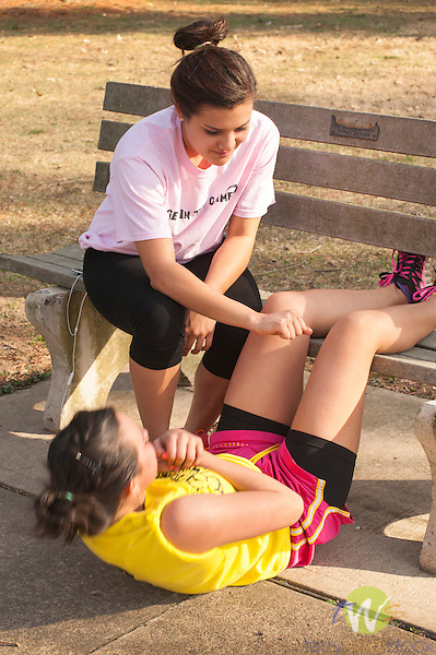 Jade Ontiveros with sister Wynd Ontiveros doing crunches with park bench.