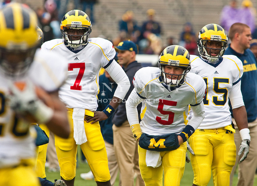 Michigan quarterback Devin Gardner (7), quarterback Tate Forcier (5), and running back Michael Cox (15) watches teammates run through warm up drills before the Wolverines' spring football game, Saturday, April 17, 2010, in Ann Arbor, Mich. (AP Photo/Tony Ding)