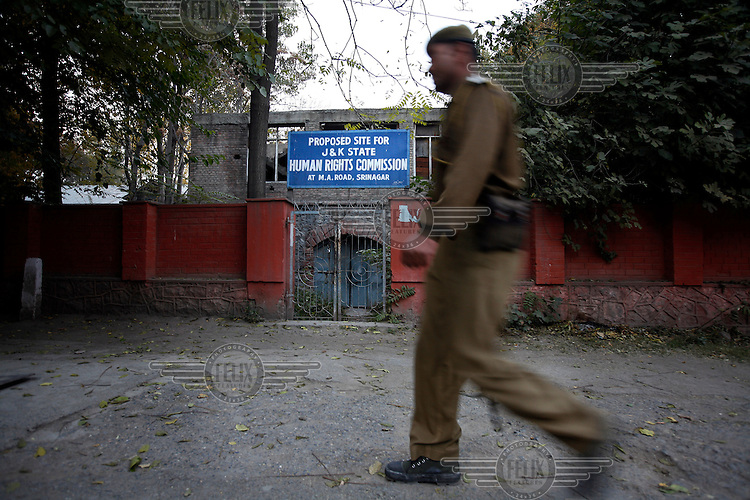 A paramilitary policeman passes a ruined building building, the proposed site for Jammu and Kashmir Human Rights Commision.  Srinagar, Kashmir,India. © Fredrik Naumann/Felix Features