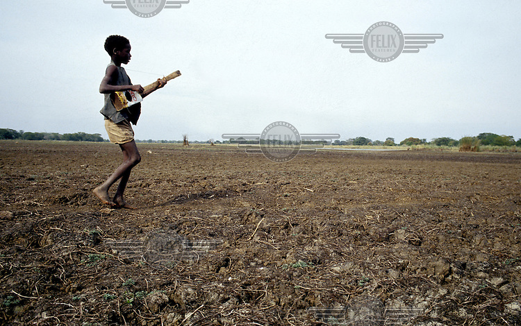 A young boy plays a home made guitar as he walks through a dry river bed.