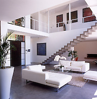 A modern open plan living room with a staircase to one side that leads up to a gallery walkway around the upper floor. The room is simply furnished with white upholstered seating arranged around a transparent coffee table.