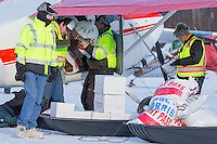 Volunteers help Volunteer Iditarod Air Force pilot, John Norris load his plane with musher drop bags, people food and HEET for a trip to the Rainy Pass checkpoint at the Willow, Alaska airport during the Food Flyout on Saturday, February 20, 2016.  Iditarod 2016