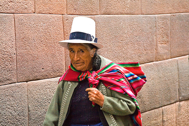 PERUVIAN WOMAN WALKS THE WALLED STREETS OF CUZCO