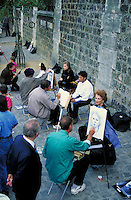 Row of portrait artists and their clients on quais along Seine. Passersby. Paris, France.