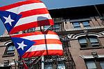 Cuban flags fly across Grand Street, Williamsburg against a blue sky near the East River in Brooklyn, New York.