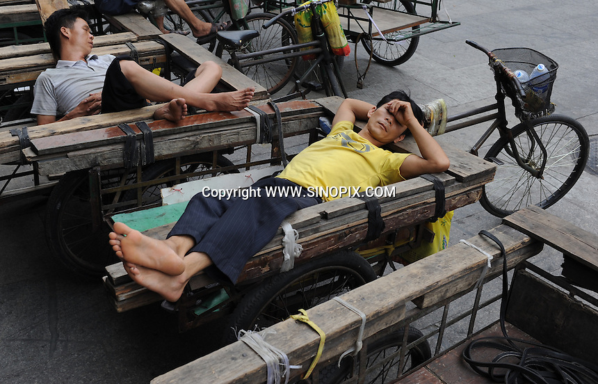 Delivery men sleep on the street in Guangzhou, China.  The delivery men who normally bicycle around all kinds of merchandise for western businessmen at wholesale markets have seen less work as the recession has slowed exports from China..12 Sep 2009