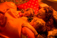 A woman breastfeeds two of her daughters at the same time - one 20 months and one 4 years old. She is feeding them off to sleep at bedtime.<br /> <br /> 07/02/2013<br /> Hampshire, England, UK