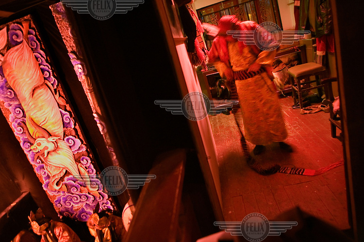 A performer in the changing rooms of the Dongba Palace, where a nightly show for tourists illustrates an important aspect of Nakhi (Naxi) culture. Dongba religion is a form of shamanism, and a Dongba shaman is a witch doctor, scholar, craftsman and artist, charged with disseminating Dongba culture. There are now very few Dongba shamans, as many of the younger generation have no interest in following this tradition.
