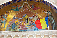 """Romania. Iași County. Iasi. Religious scenery and Romanian flag above the entrance to  the Orthodox Church """"Saint Nektarios"""". The national flag of Romania is a tricolor with vertical stripes, beginning from the flagpole: blue, yellow and red. Iași (also referred to as Iasi, Jassy or Iassy) is the largest city in eastern Romania and the seat of Iași County. Located in the Moldavia region, Iași has traditionally been one of the leading centres of Romanian social, cultural and artistic life. The city was the capital of the Principality of Moldavia from 1564 to 1859, then of the United Principalities from 1859 to 1862, and the capital of Romania from 1916 to 1918. 6.06.15 © 2015 Didier Ruef"""