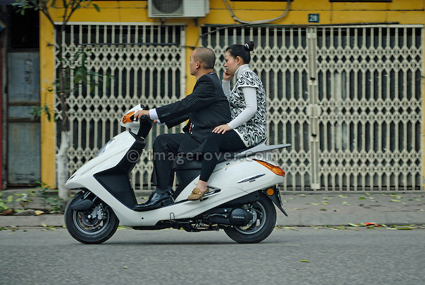 Asia, Vietnam, Hanoi. Hanoi old quarter. Young couple on motorbike rushing through Hanoi.